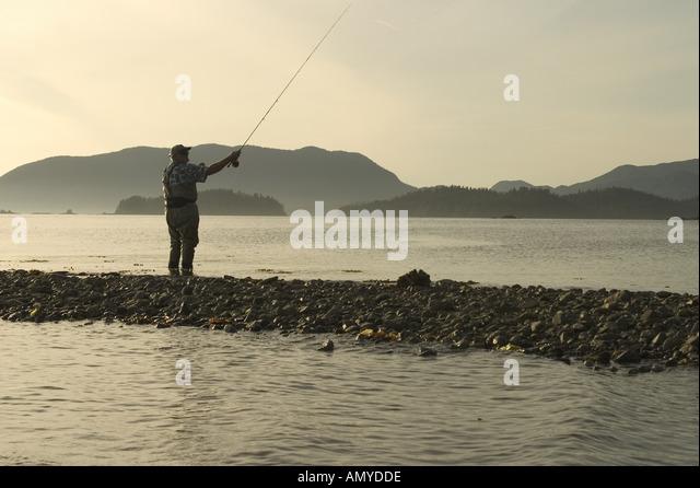 Man Flyfishing Shoreline of Sitka Sound SE AK Summer Near Harbor Pt Silhouette - Stock-Bilder