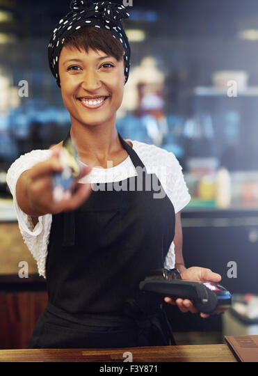 Enthusiastic pretty African American small business owner with a lovely vivacious smile handing back a credit card - Stock Image