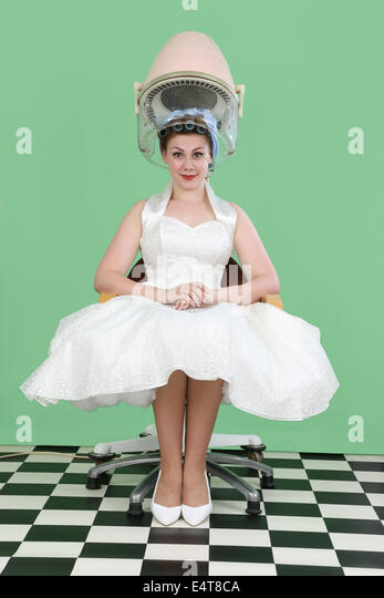 Woman in 1950s style wedding dress sitting under a vintage salon hair drier - Stock Image