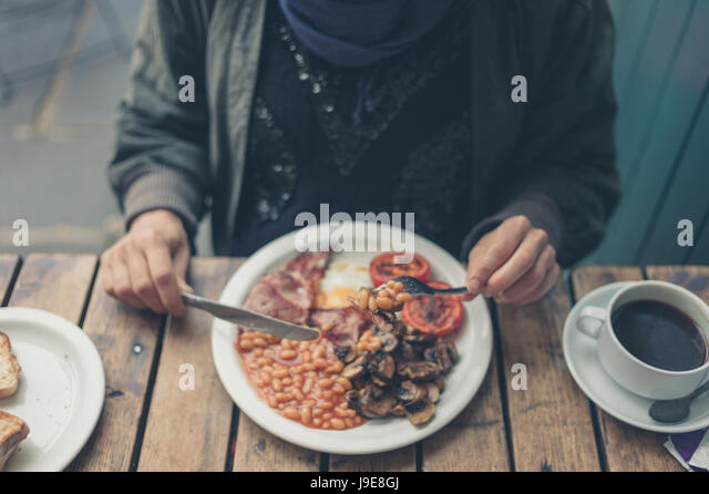 A young woman is having a traditional english breakfast - Stock Image