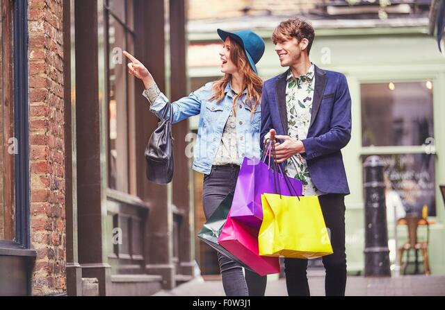 Stylish couple pointing at shop window, London, UK - Stock Image