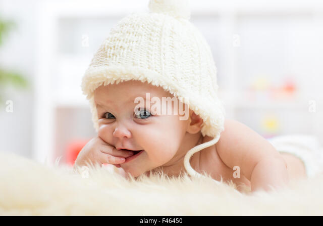 Cute little baby looking into the camera and weared in white hat. - Stock Image