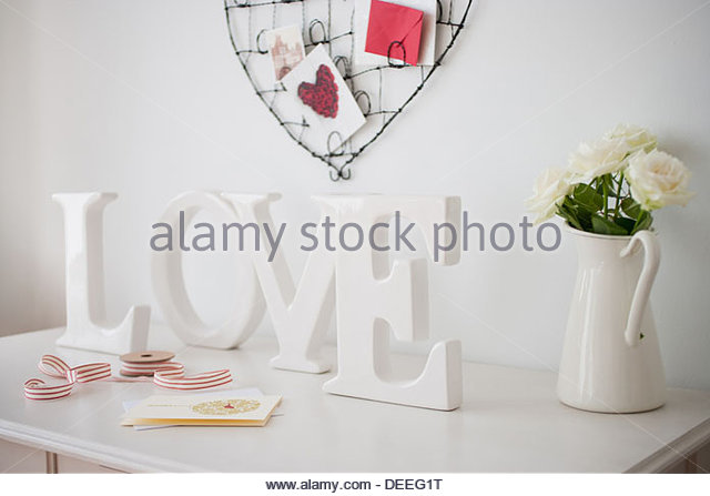 Wooden 'love' letters decoration, ribbon and cards on desk - Stock Image