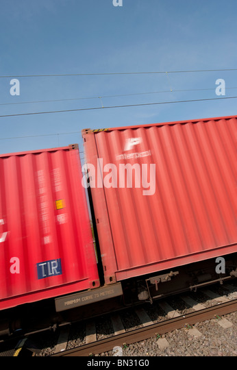 Freight containers speeding past on a train travelling along the english railway. - Stock Image