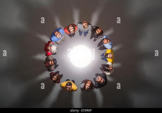 Business people around bright light - Stock Image