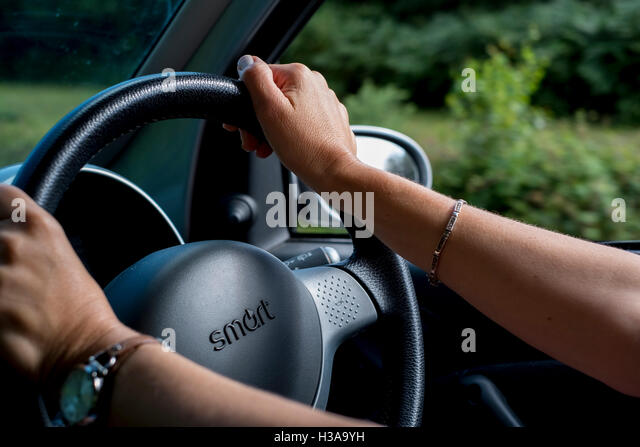 A womans hands at the wheel of a Smart car - Stock Image