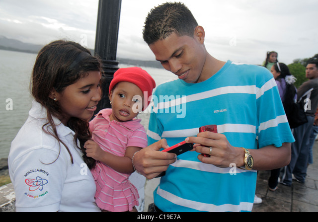 Panama City Panama Amador Panama Canal baby sister Hispanic girl boy toddler brother looking digital camera - Stock Image