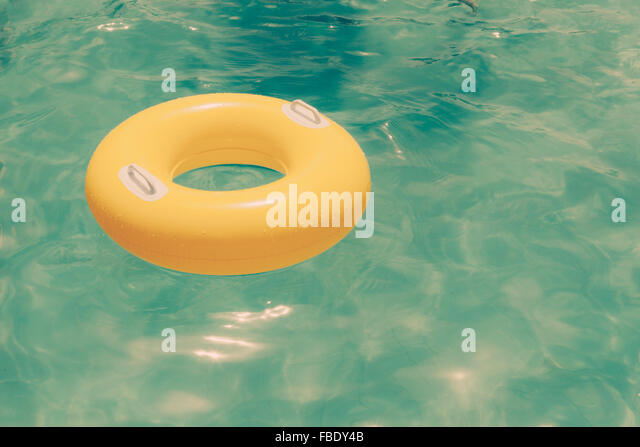 Yellow Inflatable Ring Floating At Swimming Pool - Stock Image