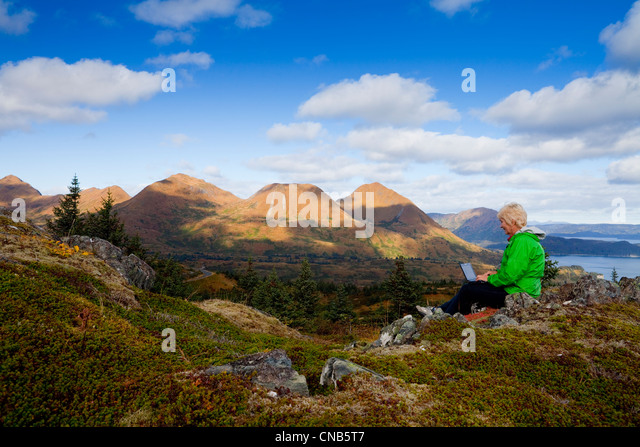 Mature woman types on laptop computer while sitting on Pillar Mountain with Monashka Bay in background, Kodiak Island, - Stock Image