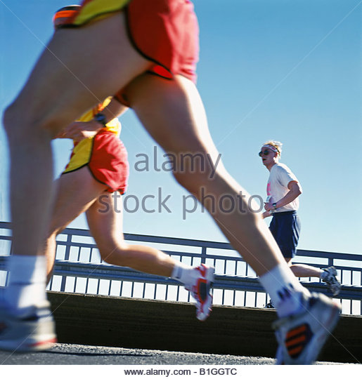 Side profile of three runners competing in a marathon - Stock Image