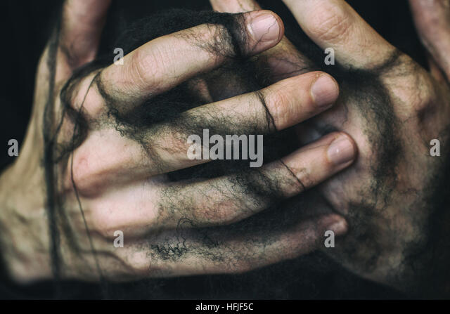 Young man's hands trapped with black spiderweb - Stock Image