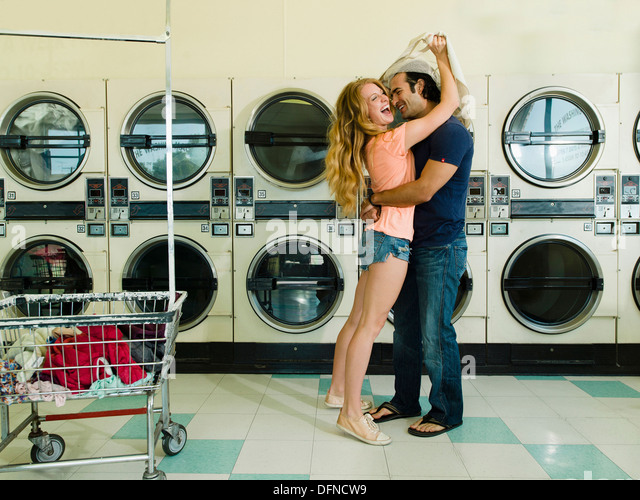 A smart young man hugs a beautiful woman in San Diego coin laundromat. - Stock Image