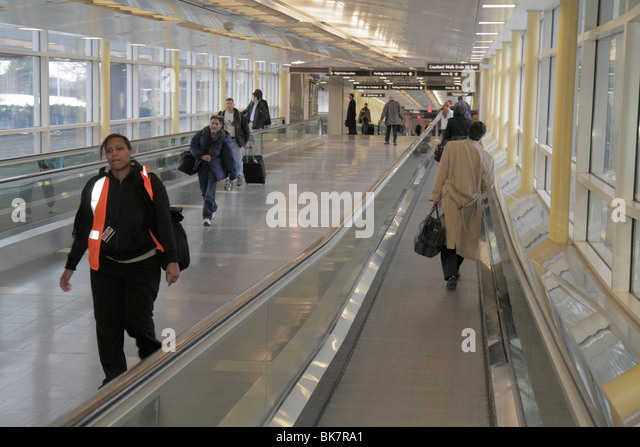Virginia Arlington Ronald Reagan Washington National Airport DCA terminal moving sidewalk Black woman man DCA worker - Stock Image