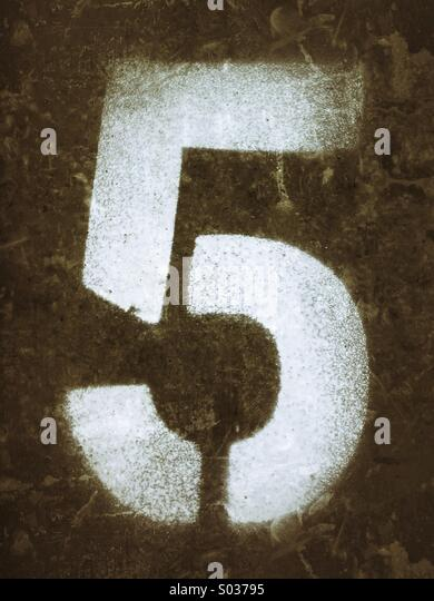 Number five spray painted in white using a stencil - Stock Image