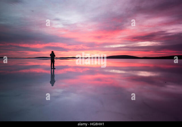 A person stands on a mirror reflected lake watching the sunset - Stock Image