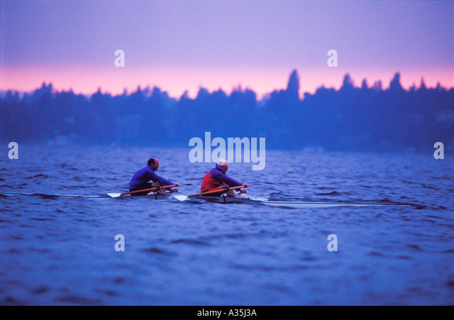 Two middle aged men row a two man shell in rough water at dawn Lake Washington Seattle - Stock Image