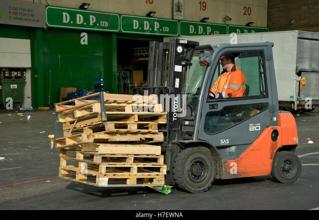 Worker shifting pallets with a fork lift truck at the New Covent Garden vegetable and fruit market. Vauxhall, London, - Stock Image