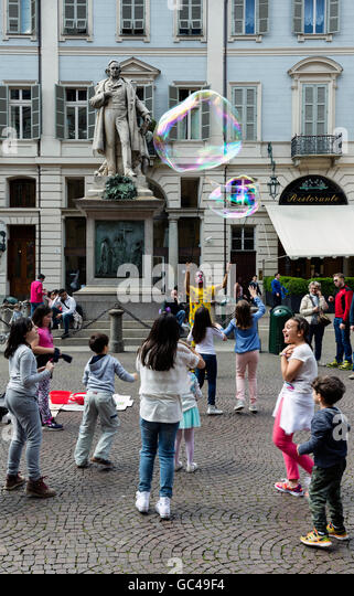 Street performer in Turin, Italy making soap bubbles for a group of children. - Stock Image