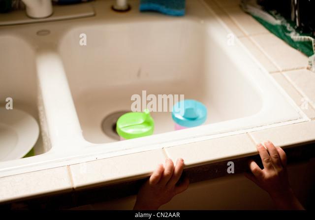 Child reaching towards kitchen sink with beakers - Stock-Bilder