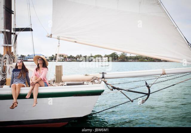 Two women on sitting on edge of sailing boat, legs dangling over the edge - Stock-Bilder