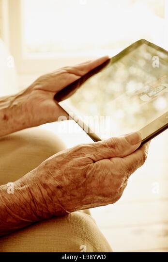 Senior person hands using a tablet computer. - Stock-Bilder