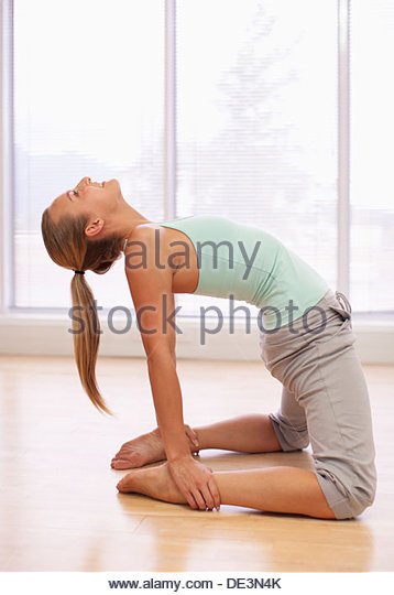 Portrait of smiling woman holding leg overhead in gymnasium - Stock Image