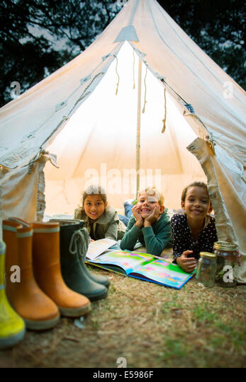 Children smiling in tent at campsite - Stock Image