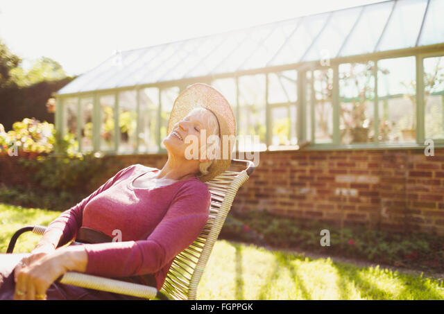 Carefree senior woman relaxing outside sunny greenhouse - Stock Image