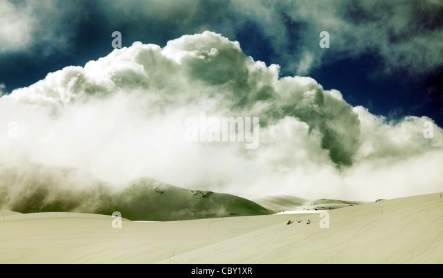 Grunge winter landscape of high mountains with snow blizzard and fresh blue sky, beautiful nature panoramic background - Stock Image