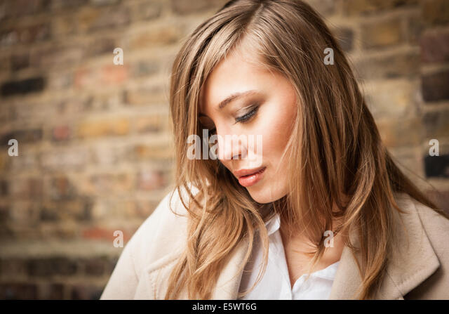 Woman with downcast eyes, brick wall in background - Stock Image