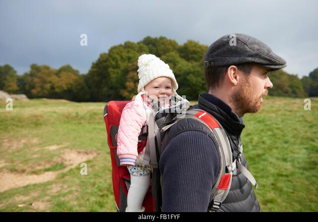 Side view of mid adult man in field wearing flat cap carrying daughter on back in baby carrier - Stock Image