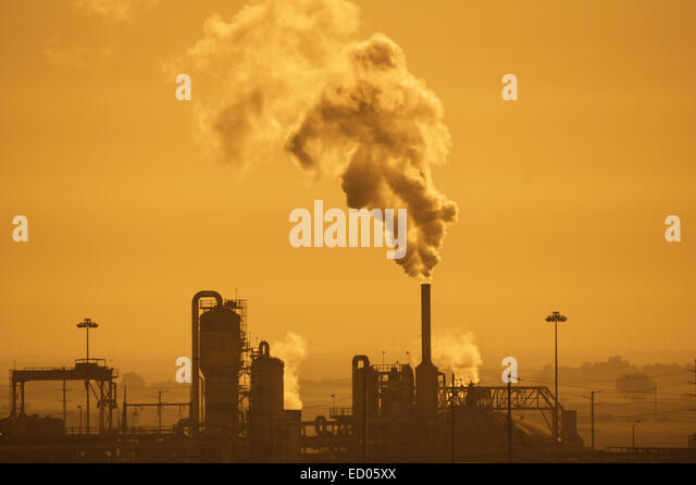 industrial plant with air pollution in a hazy orange sky - Stock Image