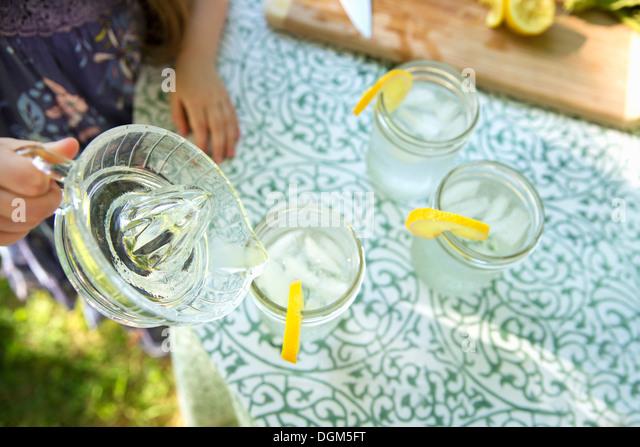 Making lemonade Overhead shot of lemonade glasses fresh slice of lemon in edge of glass child pouring drink from - Stock Image