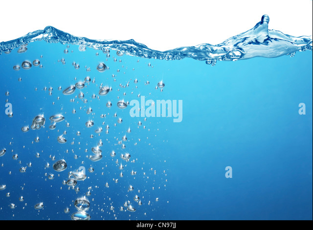 Air bubbles rise from the bottom of the ocean to the surface. Above the water is a white background. - Stock Image