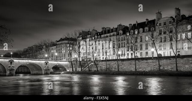 Seine River, Quai de Bourbon on Ile Saint Louis with Pont Marie and evening lights. Row of 19th century buildings, - Stock Image