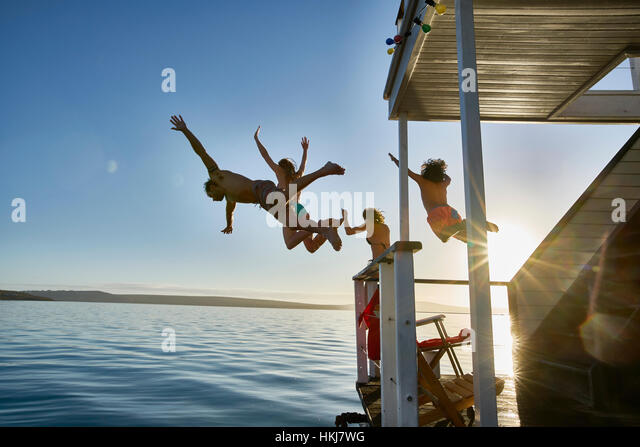 Young adult friends jumping from summer houseboat into sunny ocean - Stock-Bilder