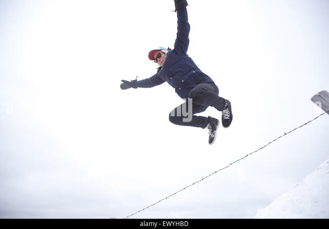 Low angle view of a young man jumping over fence - Stock Image