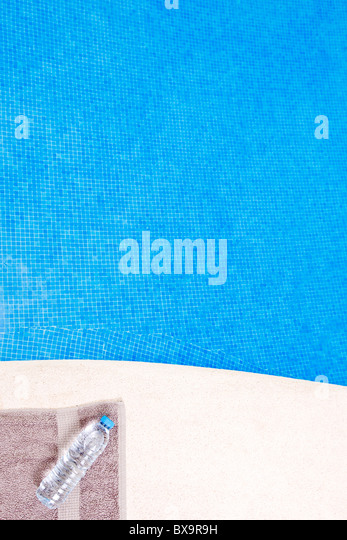 Water Bottle and Towel by the Swimming - Stock Image