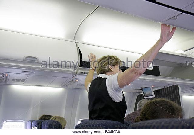 Atlanta Georgia Hartsfield-Jackson Atlanta International Airport Delta Airlines woman flight attendant shuts overhead - Stock Image