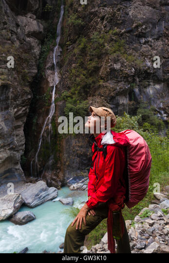 Portrait Young Pretty Girl Wearing Red Jacket Backpack Trail Mountains.Mountain Trekking Landscape WaterFall View - Stock Image