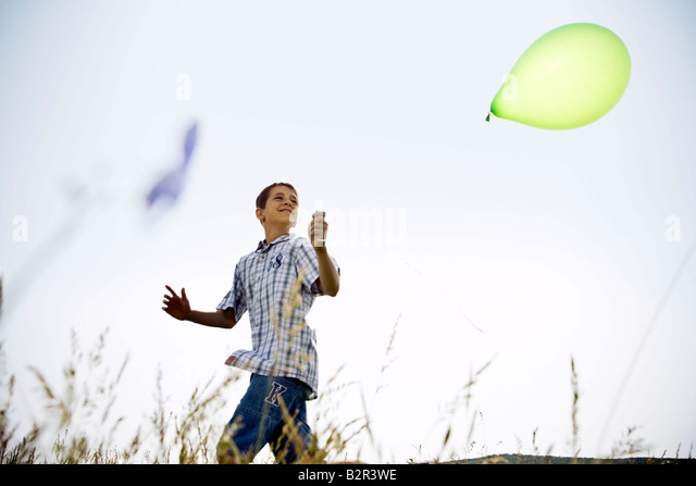 Boy running with balloon - Stock Image