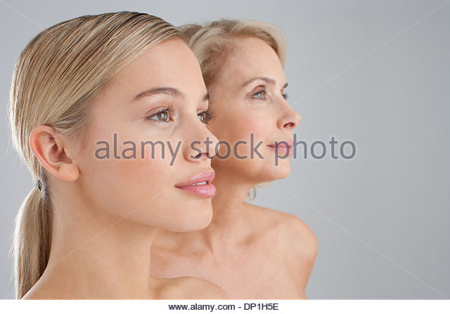 Close up of bare chested mother and daughter - Stock Image