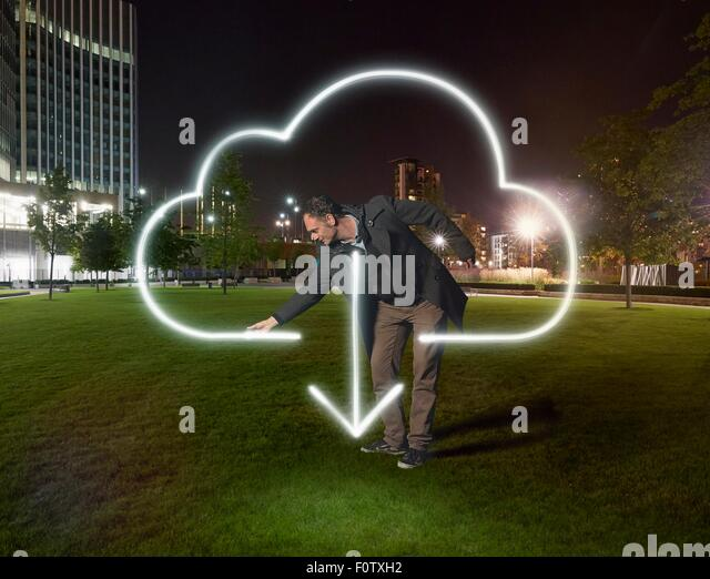 Artist painting cloud download symbol outside office building at night - Stock Image