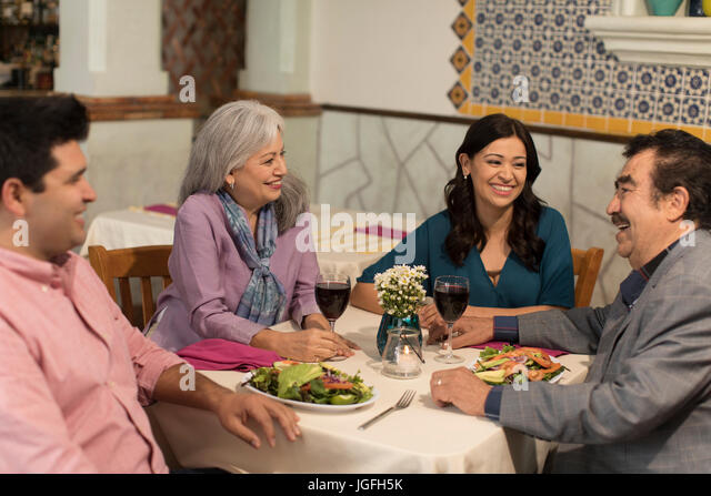 Couples laughing in restaurant - Stock Image