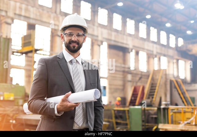 Portrait smiling manager with blueprints in steel factory - Stock Image