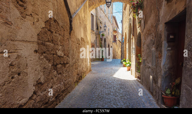Italian streets with arches on a sunny day and long shadows - Stock-Bilder
