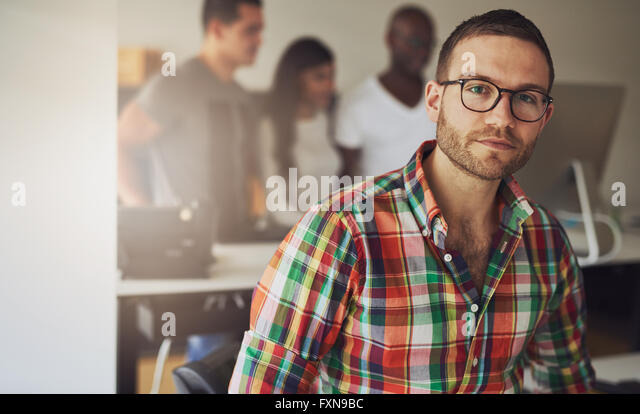 Serious single male business owner wearing multi-colored flannel button shirt with three workers on computer in - Stock Image