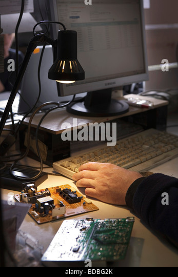 detail of worker at computer repair shop testing spare parts - Stock Image