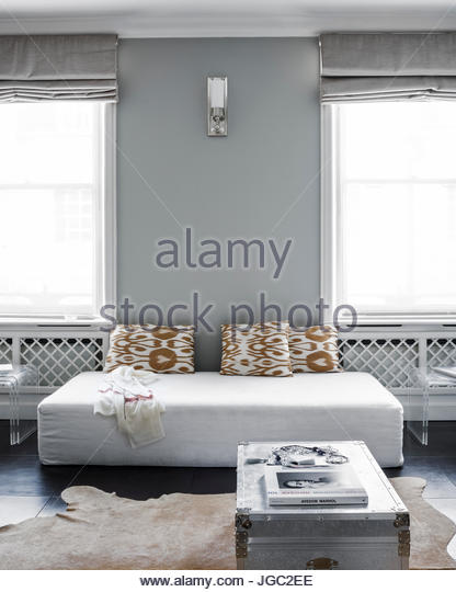 Daybed with Ikat cushions beween double windows screened in muslin - Stock Image