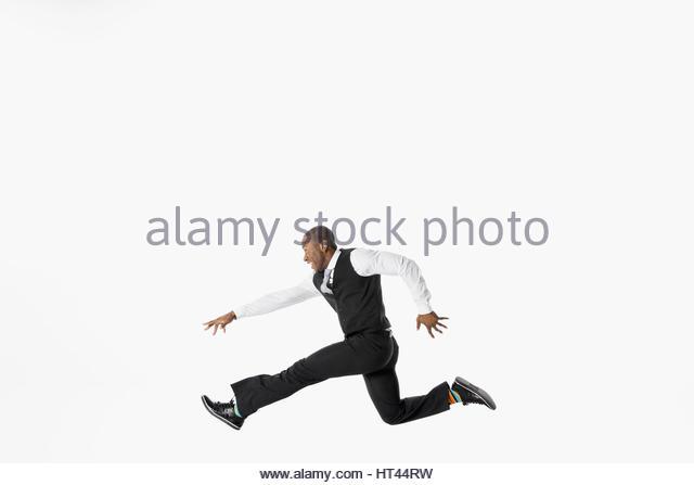 Exuberant businessman running and jumping against white background - Stock-Bilder